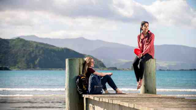 Two female students enjoying a sunny day while sitting on a jetty at Lyall Bay beach, Wellington.