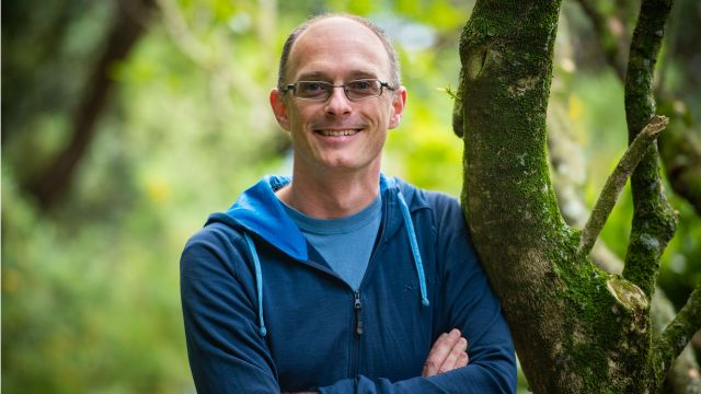 Stephen Marsland, wearing a blue hoodie, leans against a tree with green vegetation behind him.