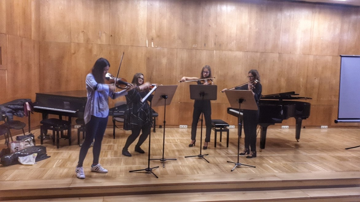Four violinists play on a stage