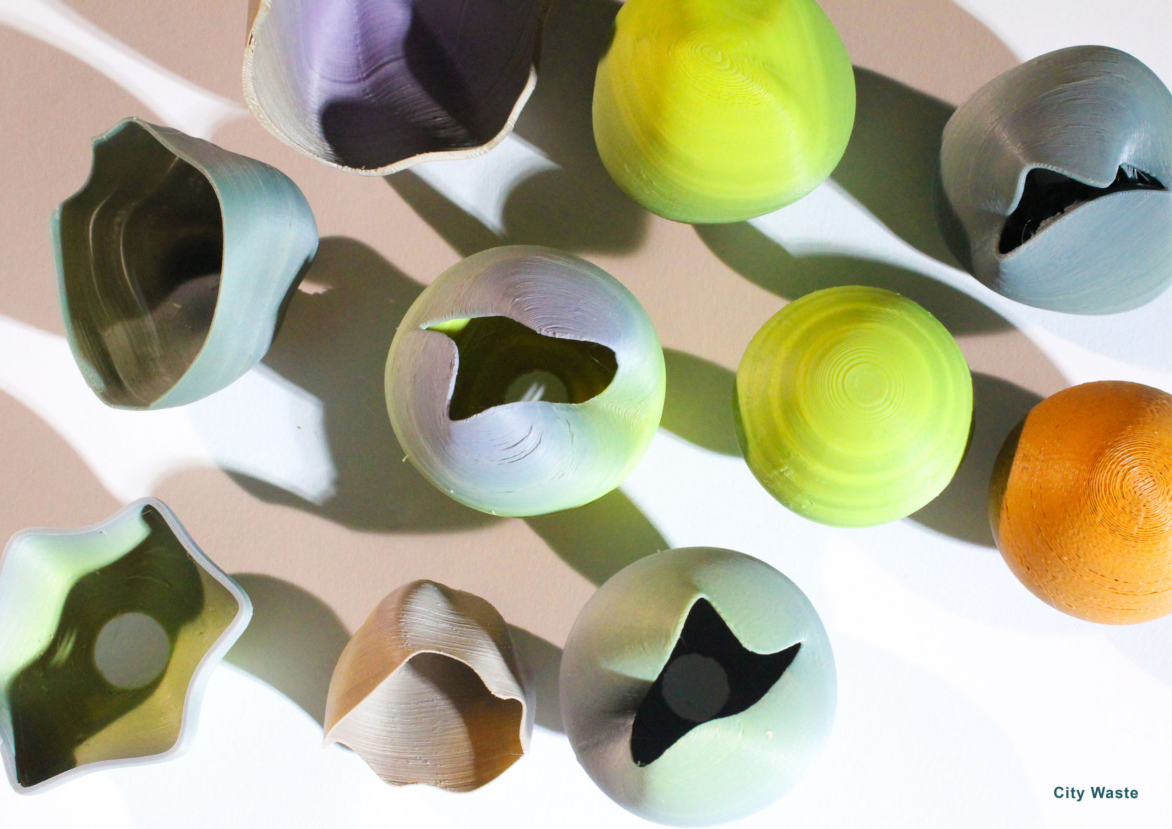 overhead view of vases and lampshades created from upcycled plastic in a variety of obre colours