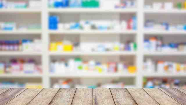 Pharmacy wall filled with medication blurred with a wooden table in the foreground