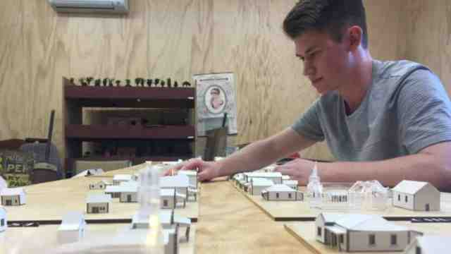 Thomas Nieuwenhuis sits with architectural model of Greytown he has created