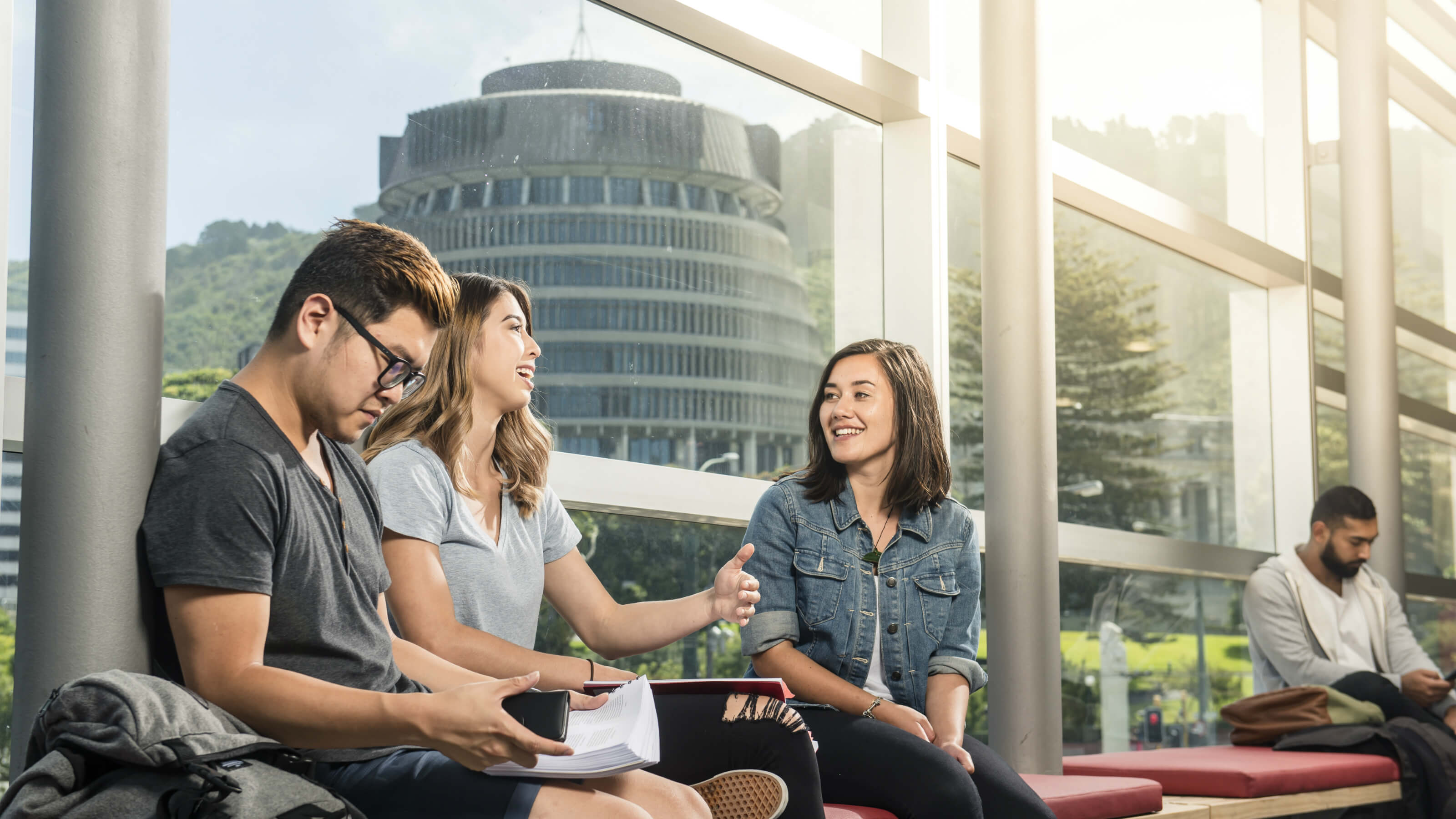 A group of students sitting and talking at Victoria University's Pipitea campus with the Beehive (Parliament buildings) in the background.
