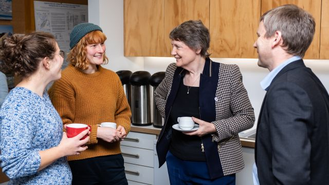 Helen Clark with three others stands by a kitchenette, chatting and holding coffee mugs