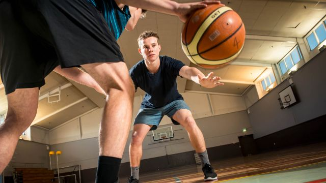 Two male students are playing one-on-one basketball at the recreation centre on Kelburn campus.