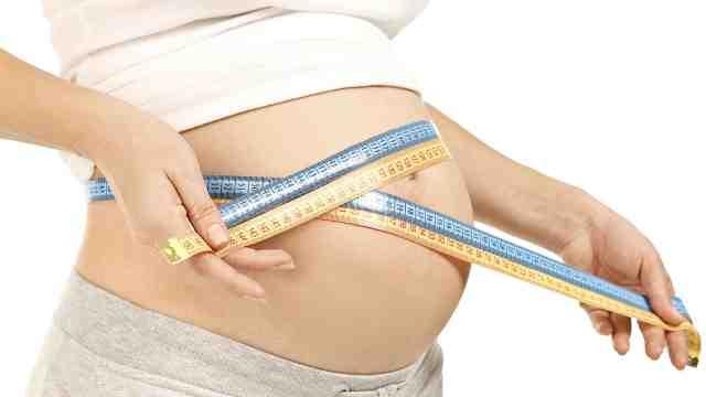 A pregnant woman measuring her abdomen.
