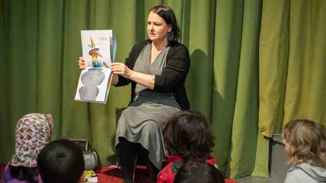 A librarian reading to a group of children.