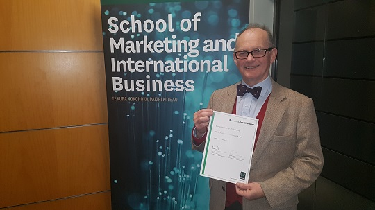 James Richard holding reviewer award certificate