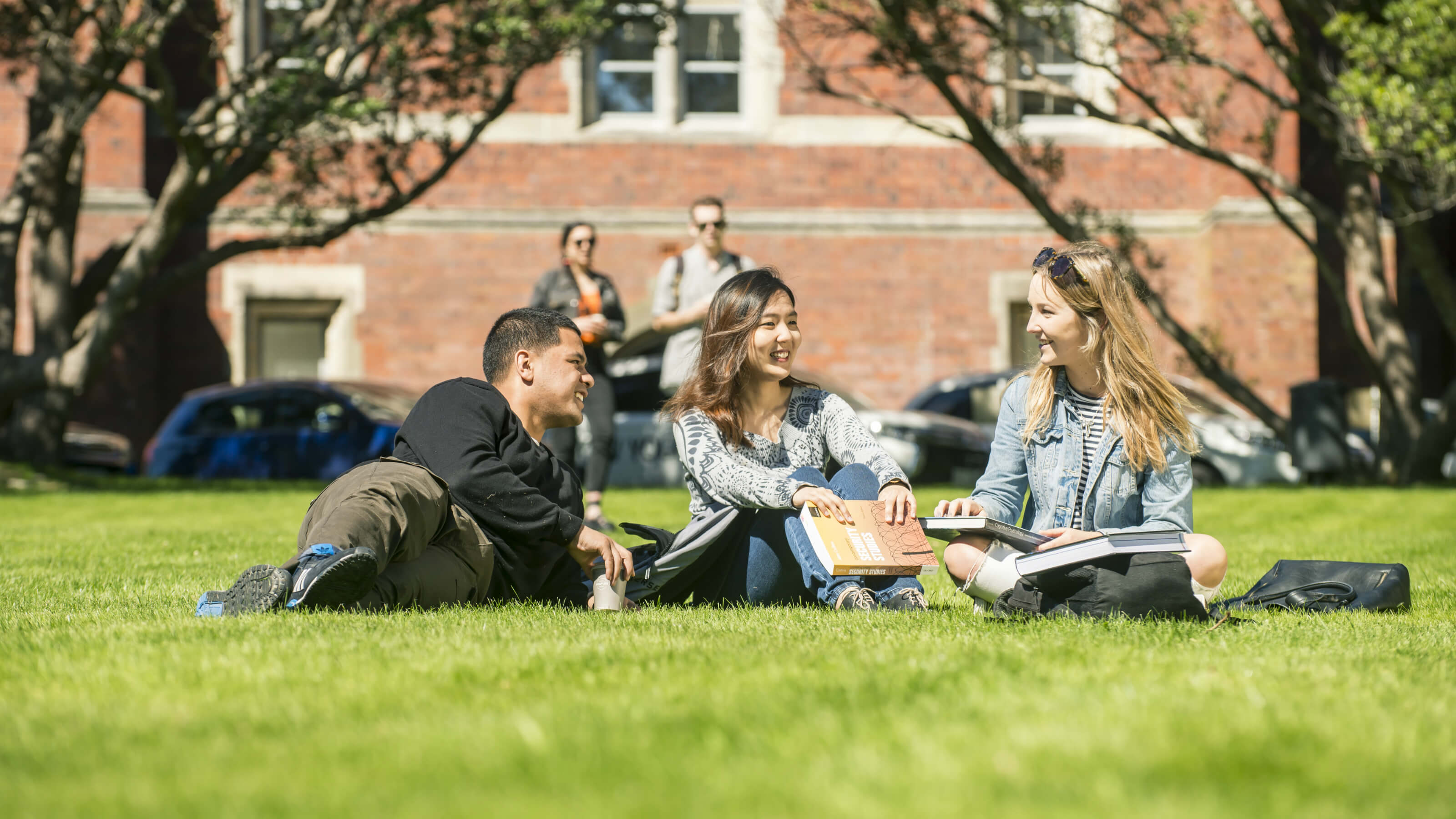 Three students sitting on the lawn in front of the Hunter Building at Victoria University's Kelburn campus