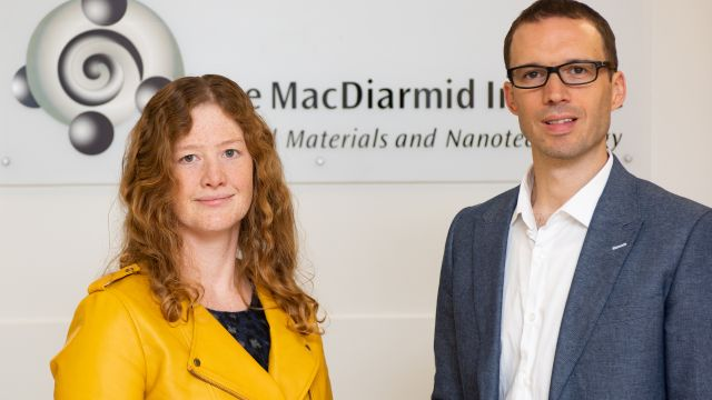 Associate Professor Nicola Gaston and Associate Professor Justin Hodgkiss stand in front of the MacDiarmid Institute name and logo