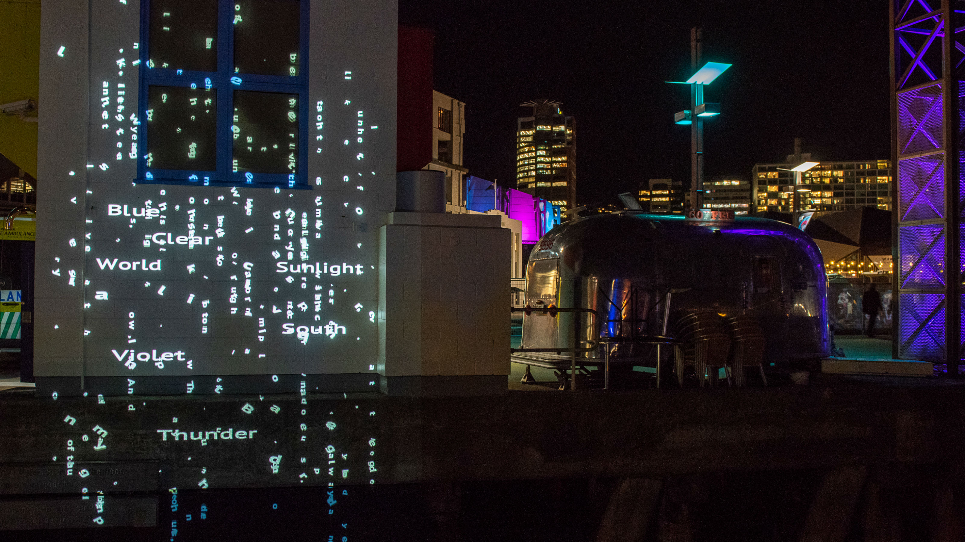 Words of light projected onto a building and Wellington harbour.