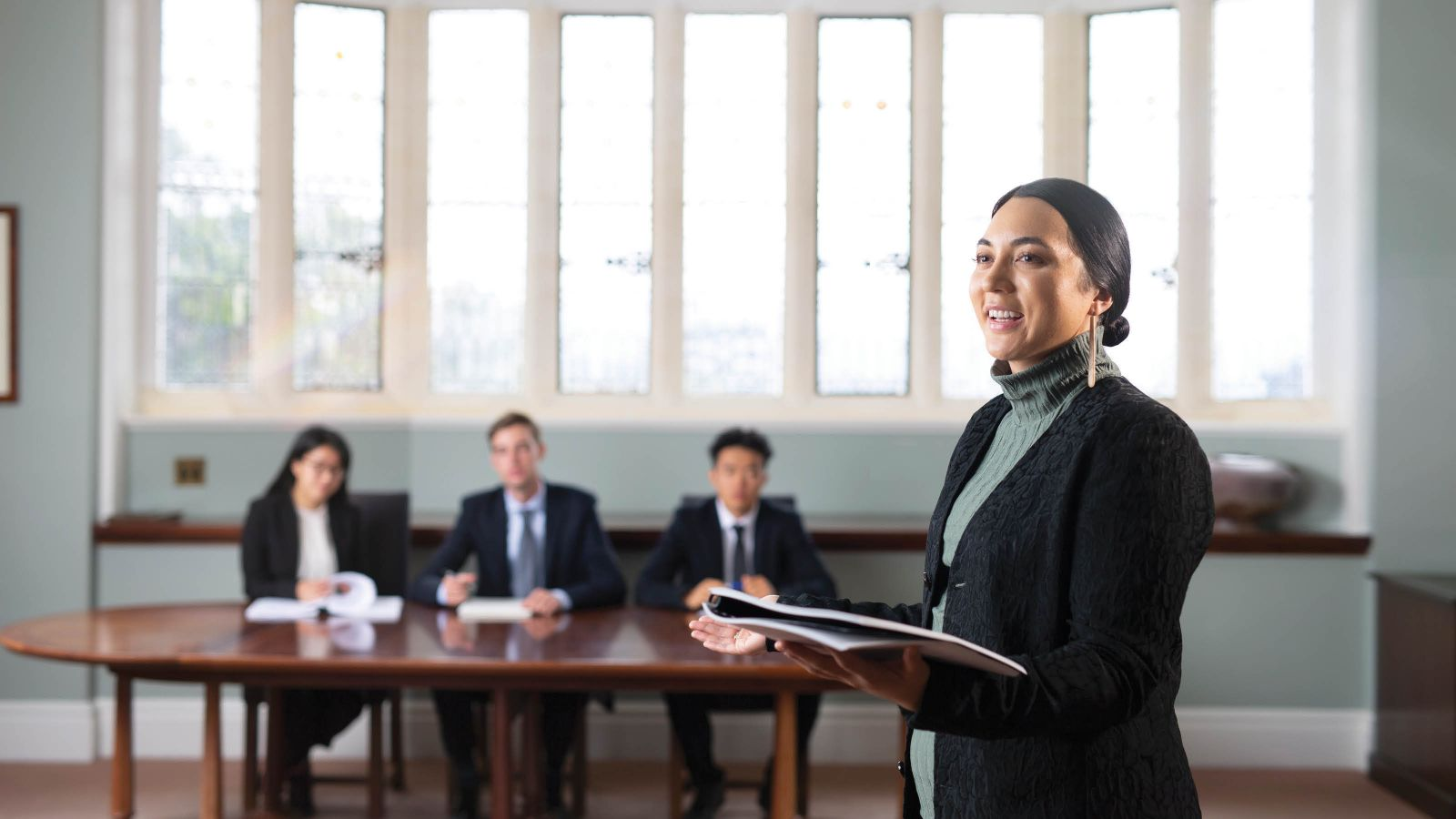 A female undergraduate law student is standing, holding a document, and mooting in front of a panel of three judges who are seated at a table.