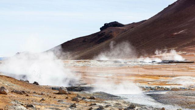 A landscape image, showing geothermal vents and bare, sandy hills
