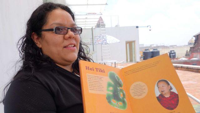 A woman holds open a book in te reo maori