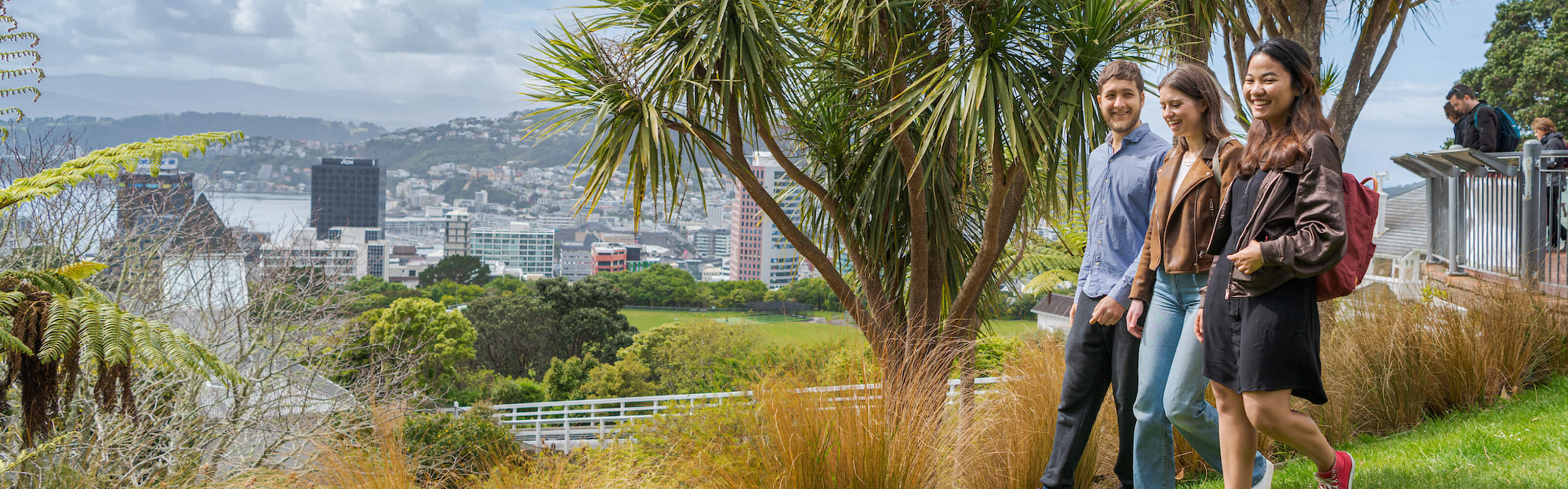 Students exploring Botanical garden with Wellington city view in background.