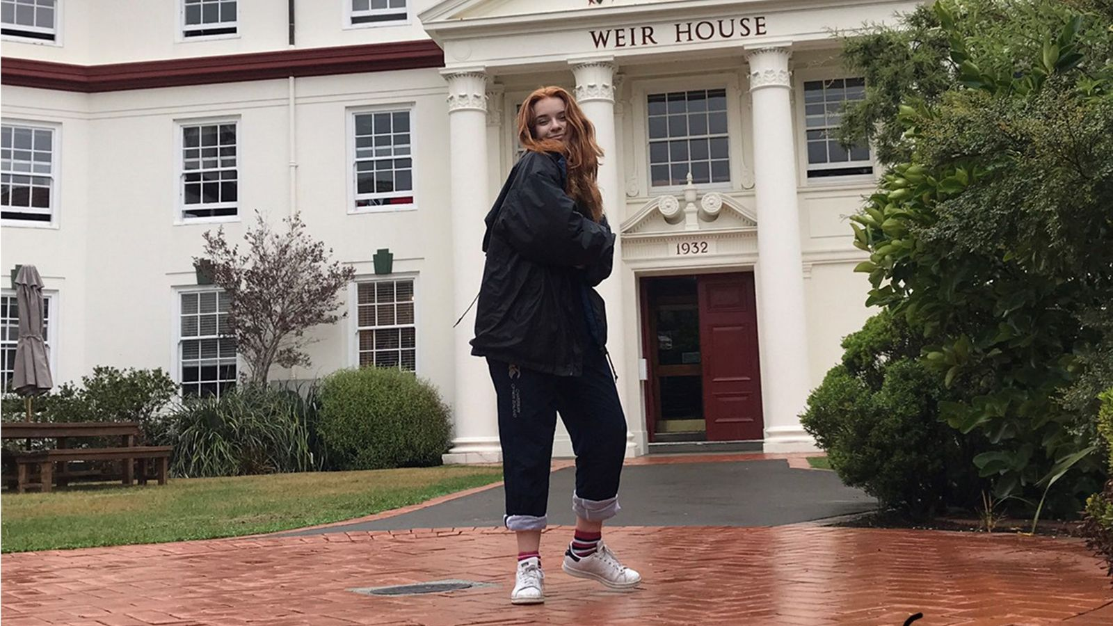 Ella stands outside of Weir House, an old white estate.