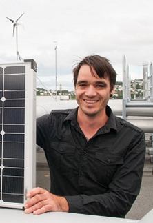 Daniel Burmester with solar panels and wind turbines in background