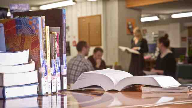 Students in library studying education books