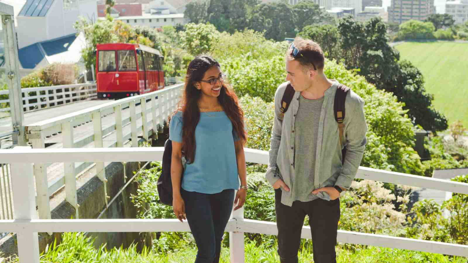 Two university students standing and talking near the cable car in Wellington.