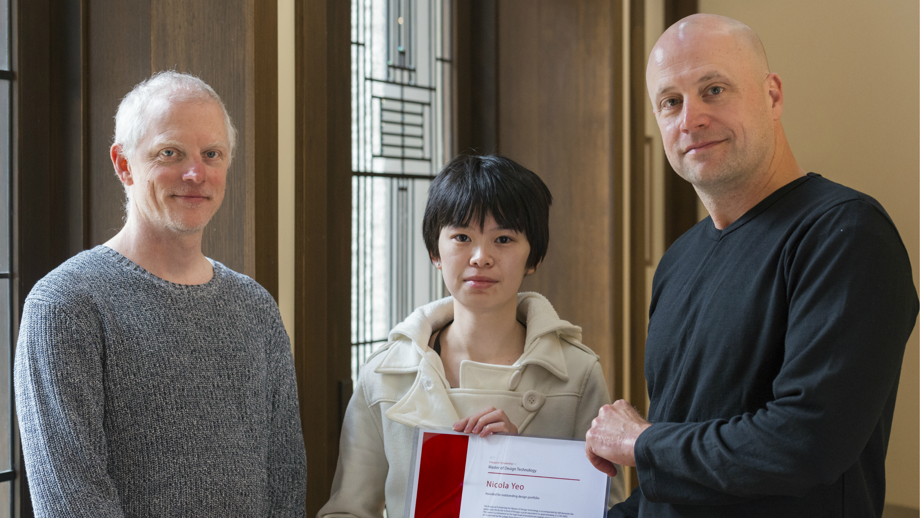 Doug Easterley handing Nicola Yeo a certificate for her scholarship, Kevin Romond stands to the left.