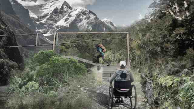 An image of the wilderness, showing snow capped mountains in the background. In the foreground is a tramping track with a wheelchair user and an able-bodied walker.