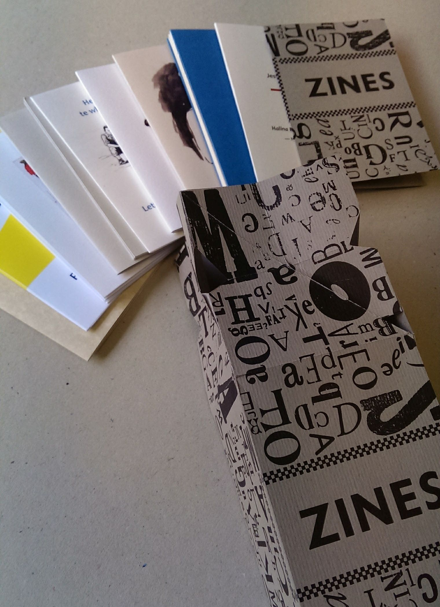 The Zine Collection box with contents spread out beside it.