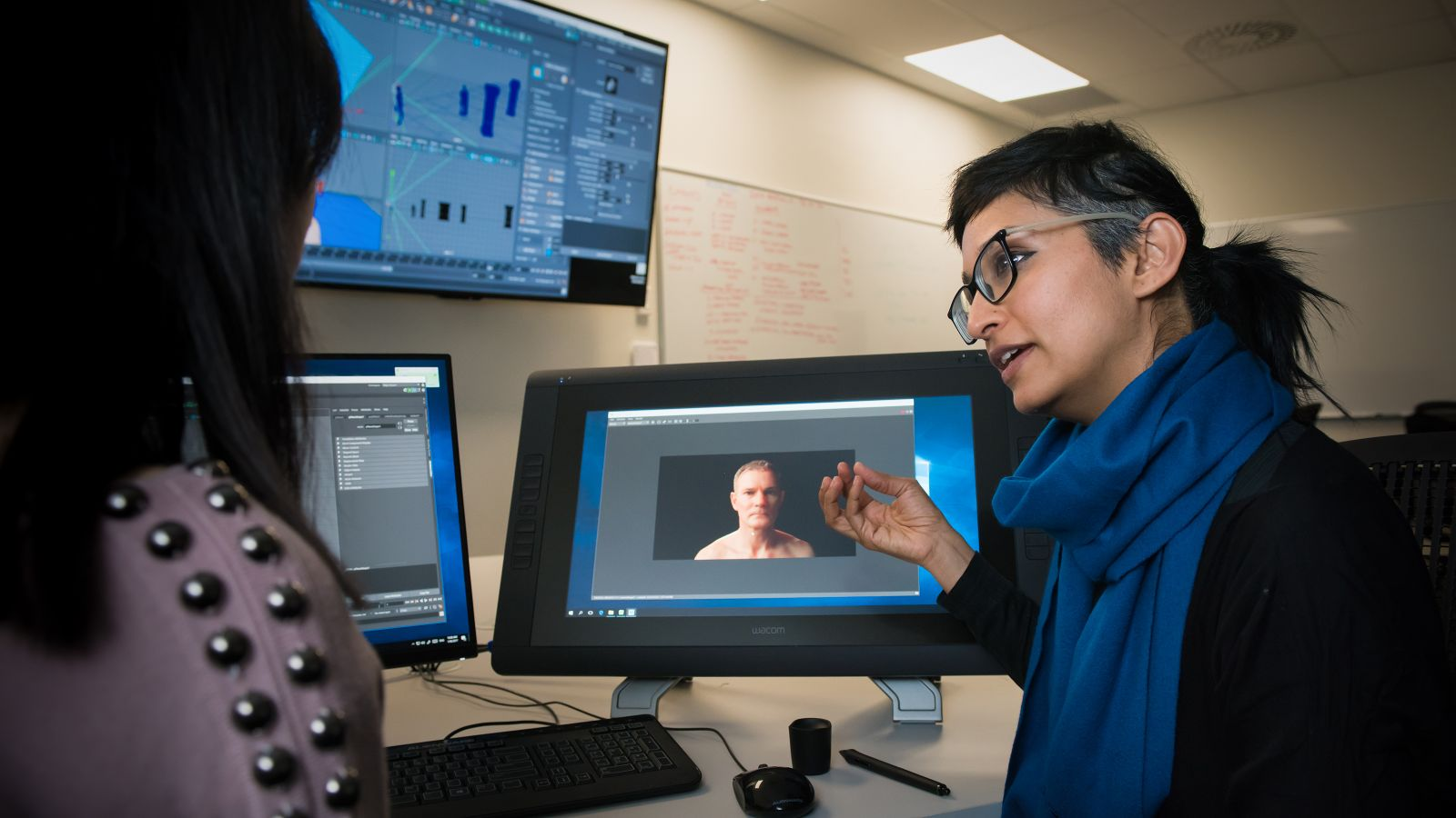 A female lecturer talks to a student with computers in the background.
