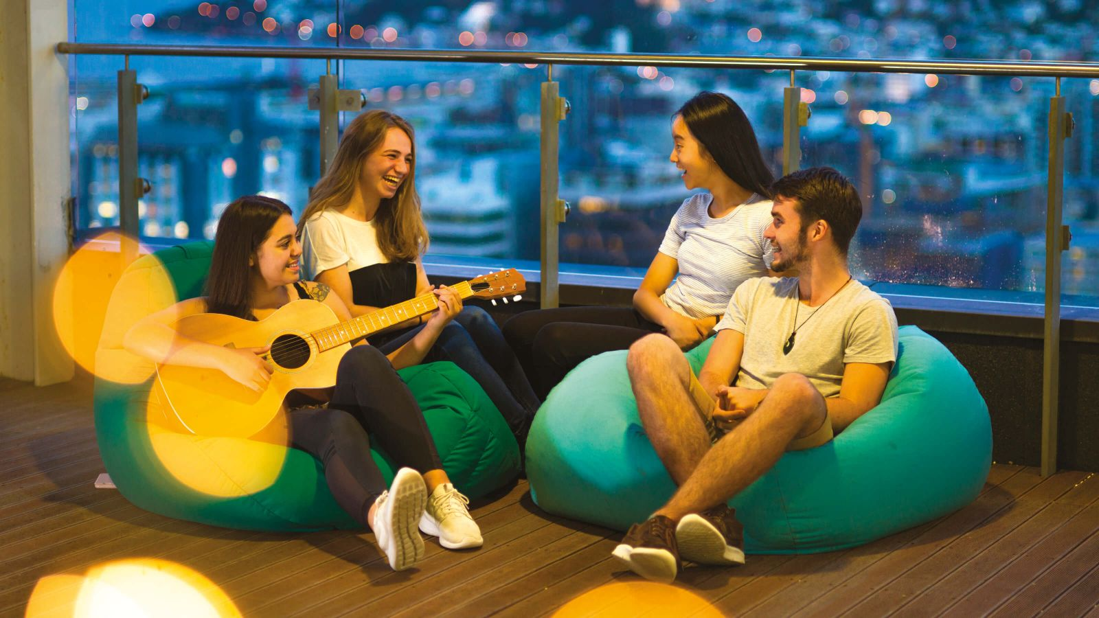 Students relaxing on bean bags on a balcony at one of Victoria University of Wellington's halls of residence.