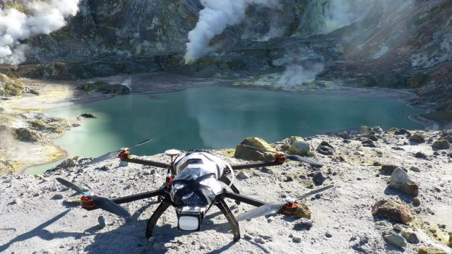 Drone perched on the edge of a smoking volcano crater