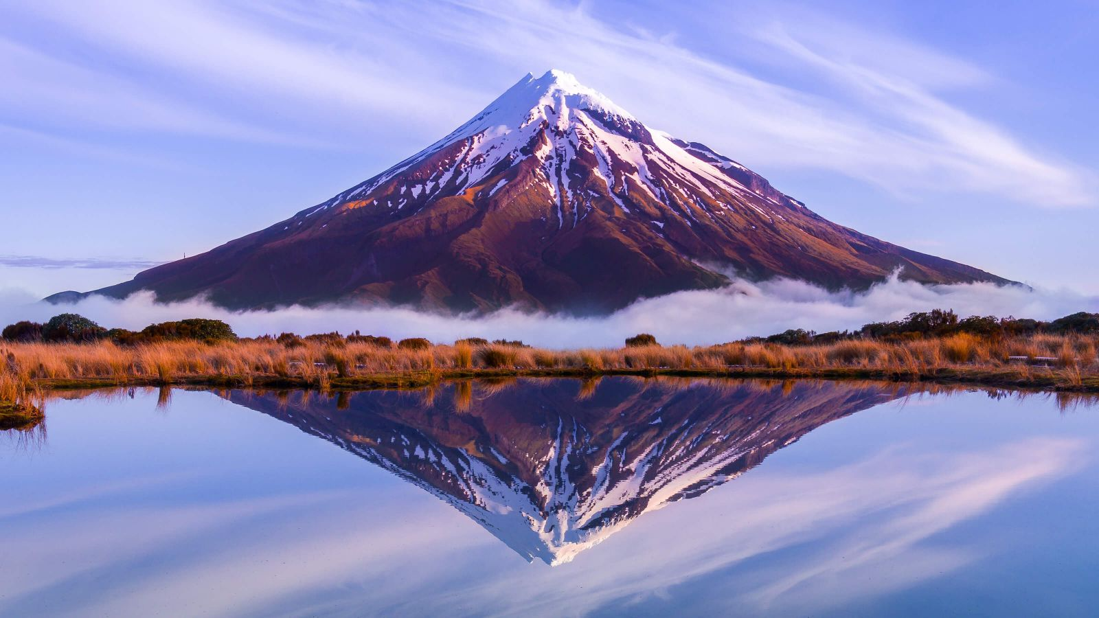 The symmetrical Mount Taranaki with its single, snowy peak extending into a soft violet sky wisped with white clouds. The entire monumental scene is perfectly reflected in the mirror of the lake separated from the mountain's base by hot orange bush and a strip of low-lying cloud.