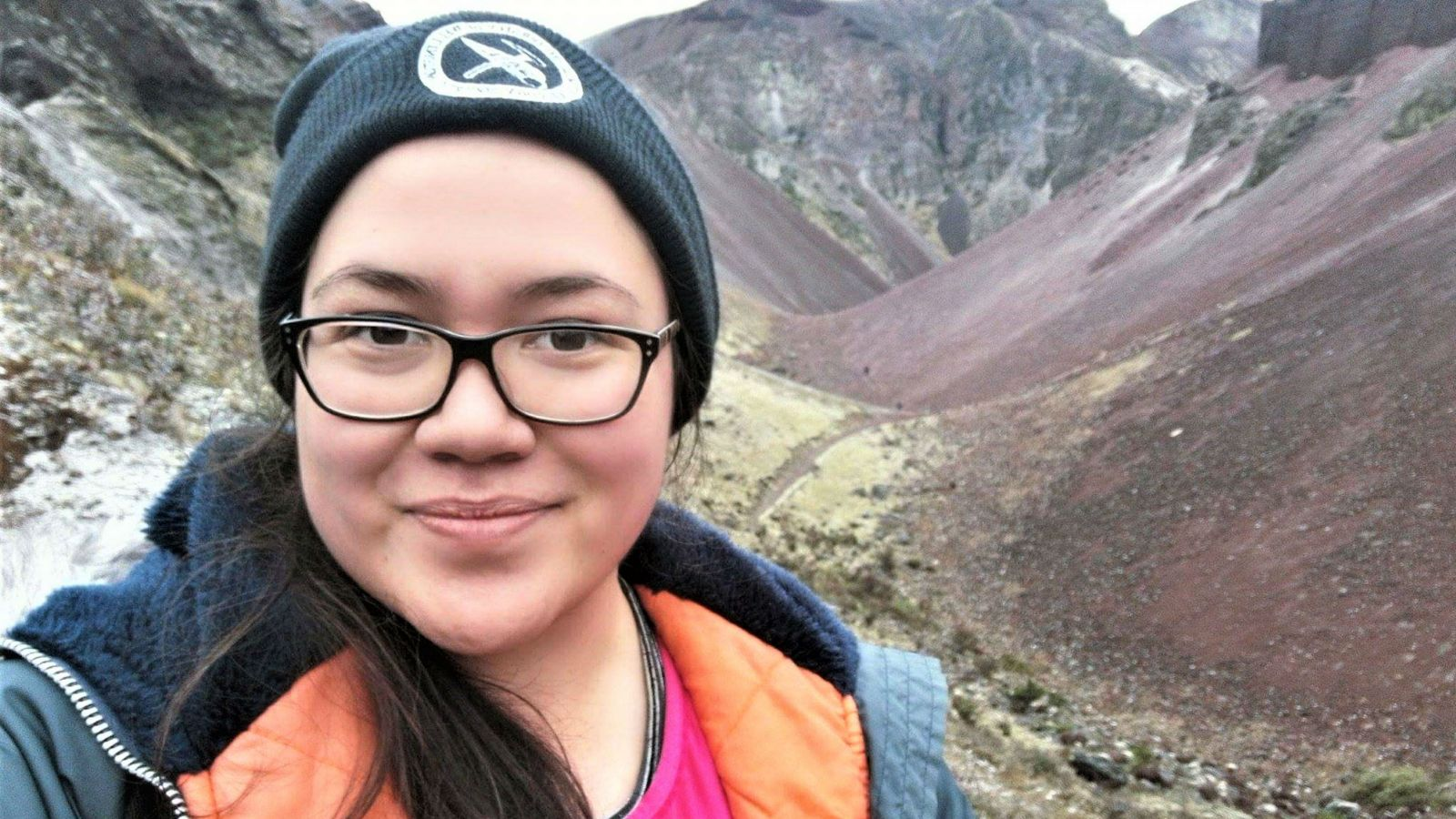 Raiatea, wearing a coat and beanie stands in front of a mountain range.