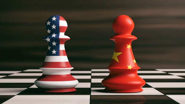Graphic of two chess pawns respectively decorated by the flags of the U.S. and China.