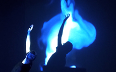 Person with arm outstretched illuminated in blue light