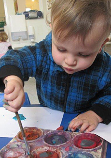 A young boy painting a picture.