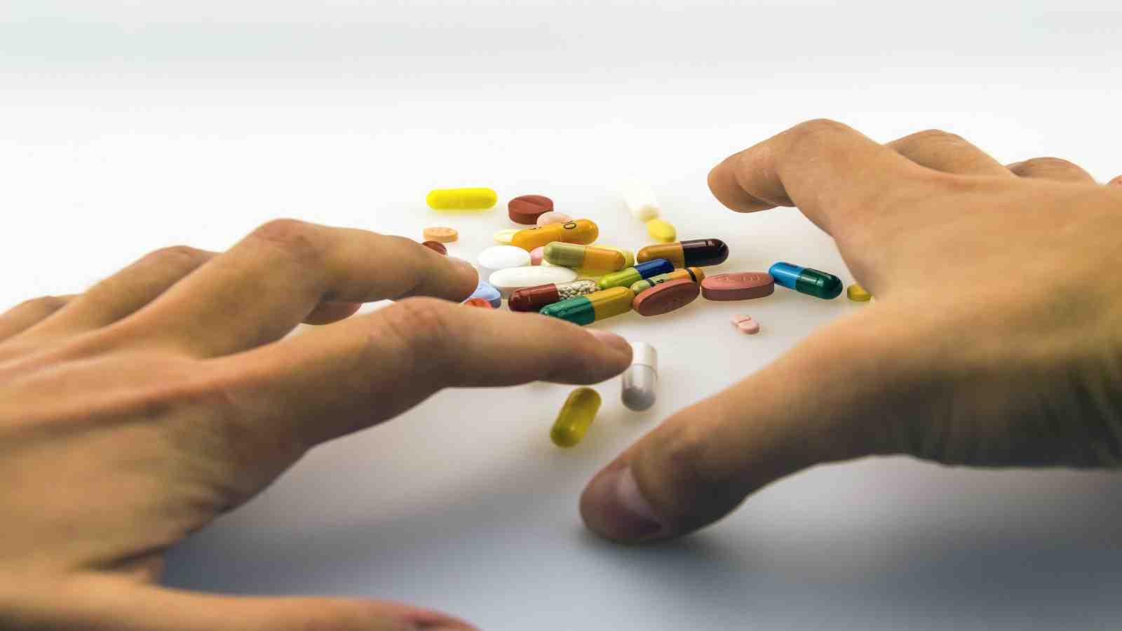 hands reaching towards pills