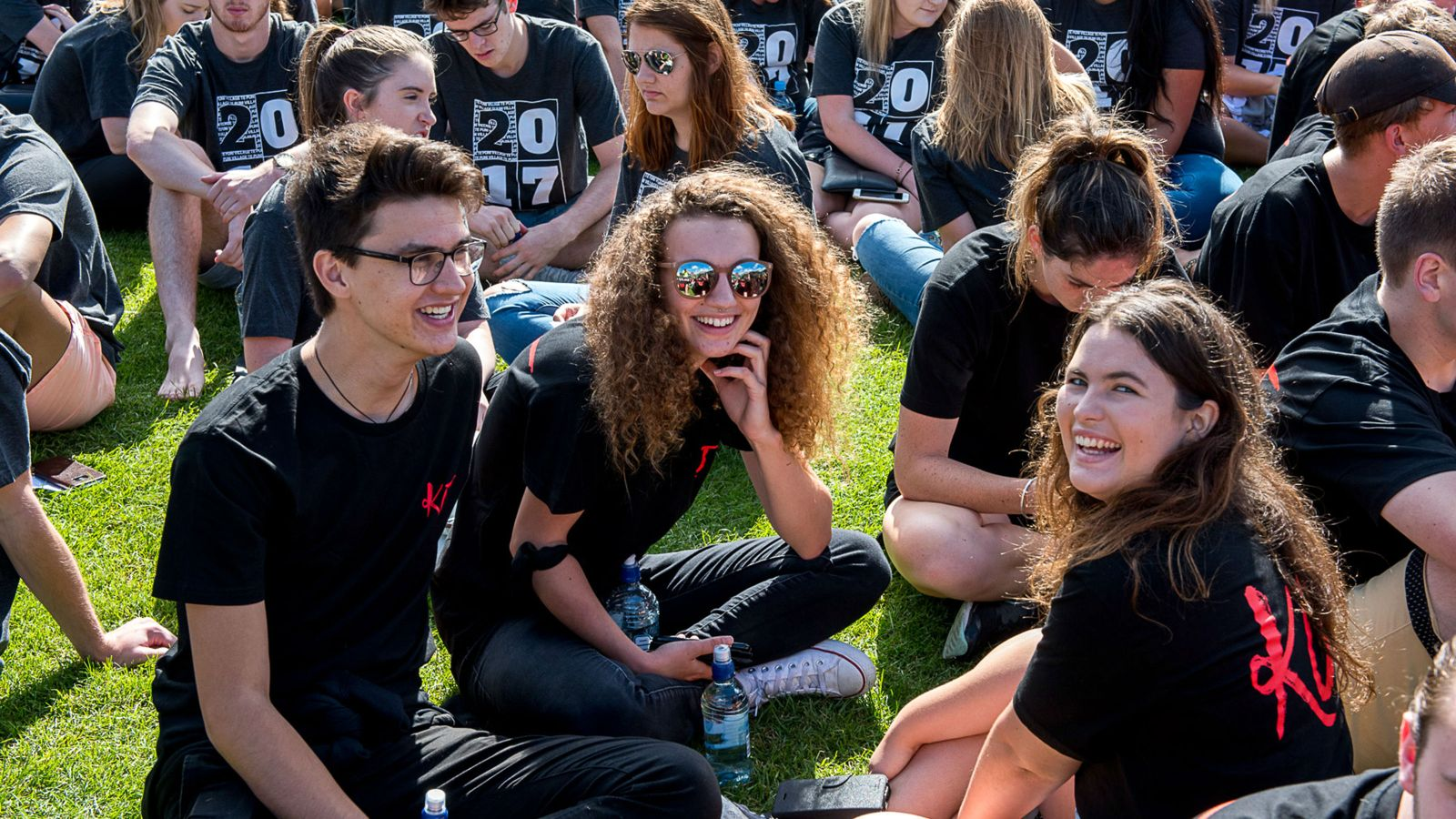 Students sitting on the grass wearing Hall tshirts at the Welcome Festival