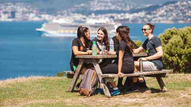 A group of students sitting at a picnic table on Matiu/Somes Island with Wellington Harbour in the background.