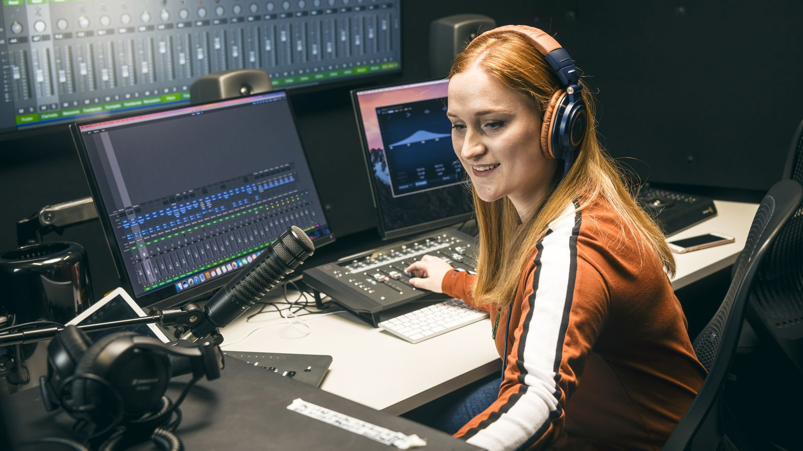 A female student with long red hair wears headphones while operating equipment in a recording studio.