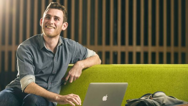 Bachelor of Science student, Max Christie, is sitting and looking up from working on his laptop in Te Toki a Rata building, Kelburn campus.