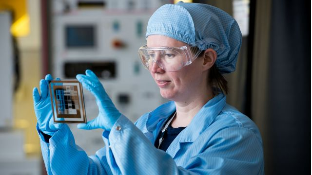 A bespectacled Dr Natalie Plank in a bouffant hair net and lab coat holds up for inspection, between latex-gloved hands, a transparent biosensor.