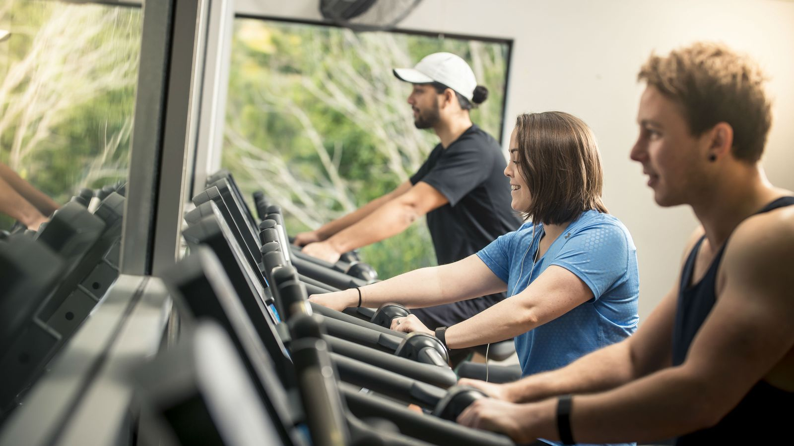 Two men and a woman working out on exercise machines.