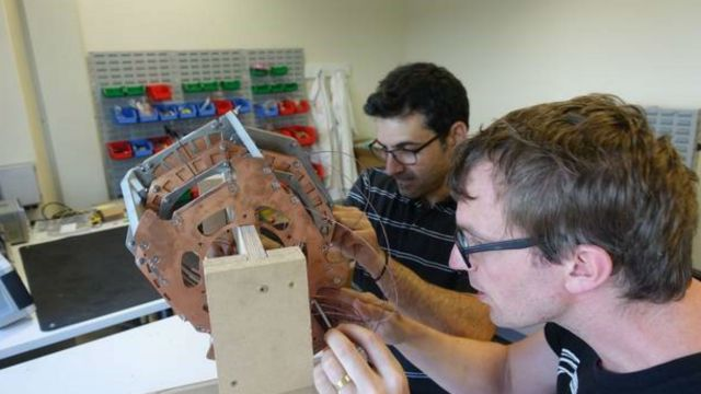 Ben Parkinson (right) and Konstantinos Bouloukakis working on the helmet-style MRI magnet.