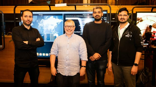 Four academics in front of a cybersecurity map