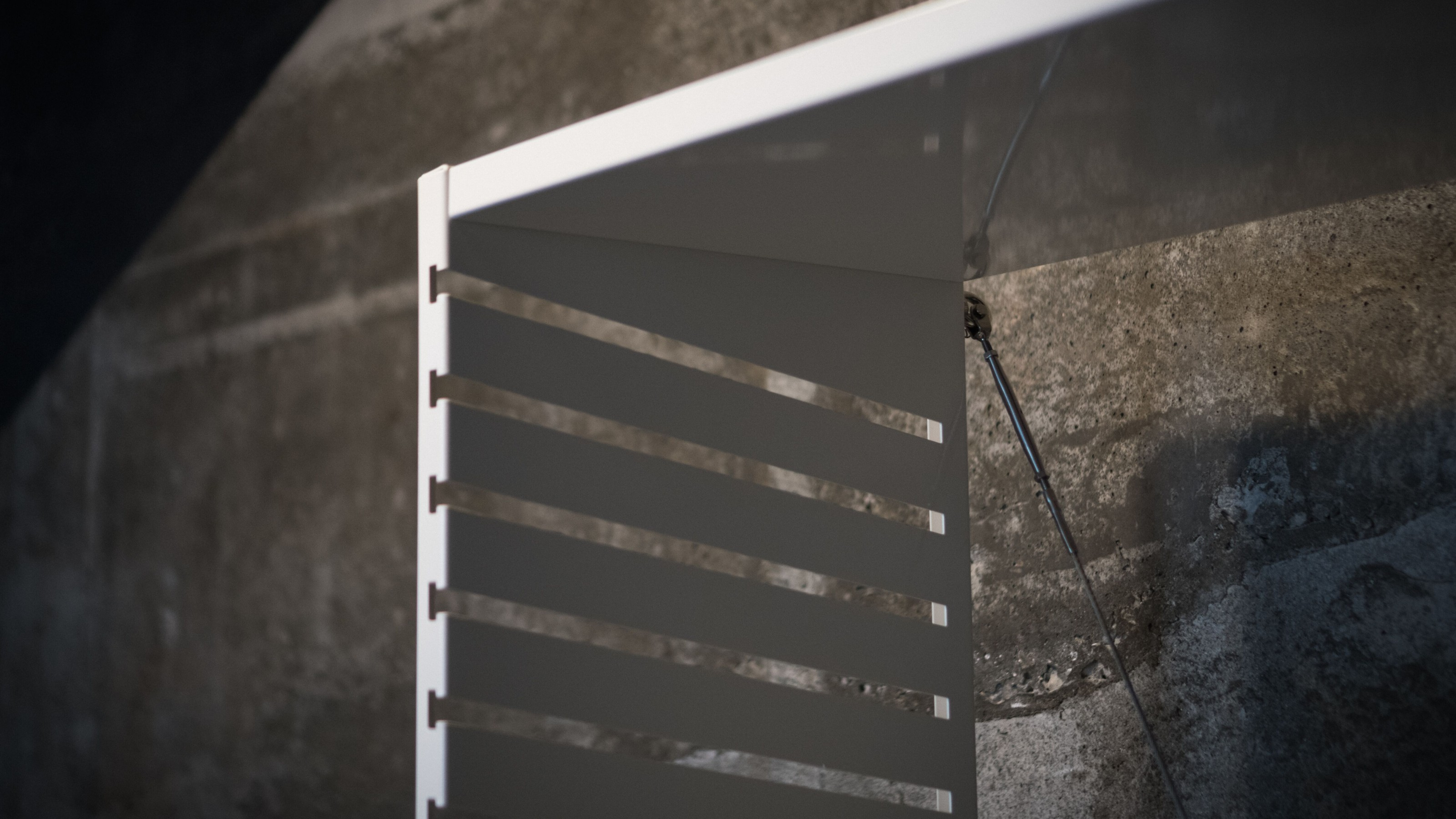 Close up of white shelf unit made of folded sheet of metal with slots to hold shelves