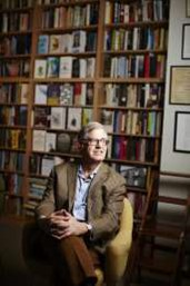 Jonathan Galassi sitting in front of a bookshelf.