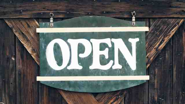 A wooden door with an open sign on it.
