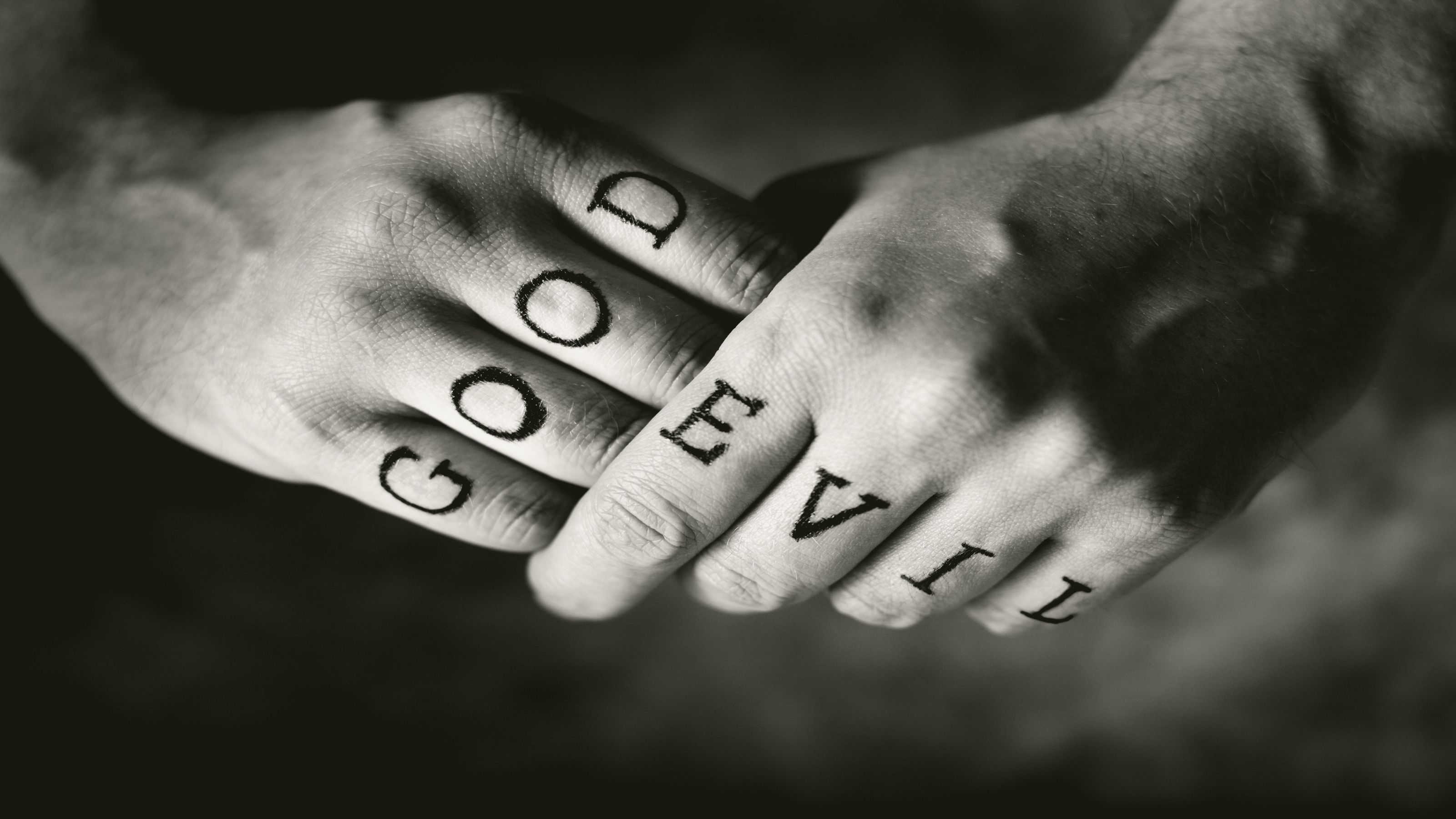 good and evil written across the knuckles of hands
