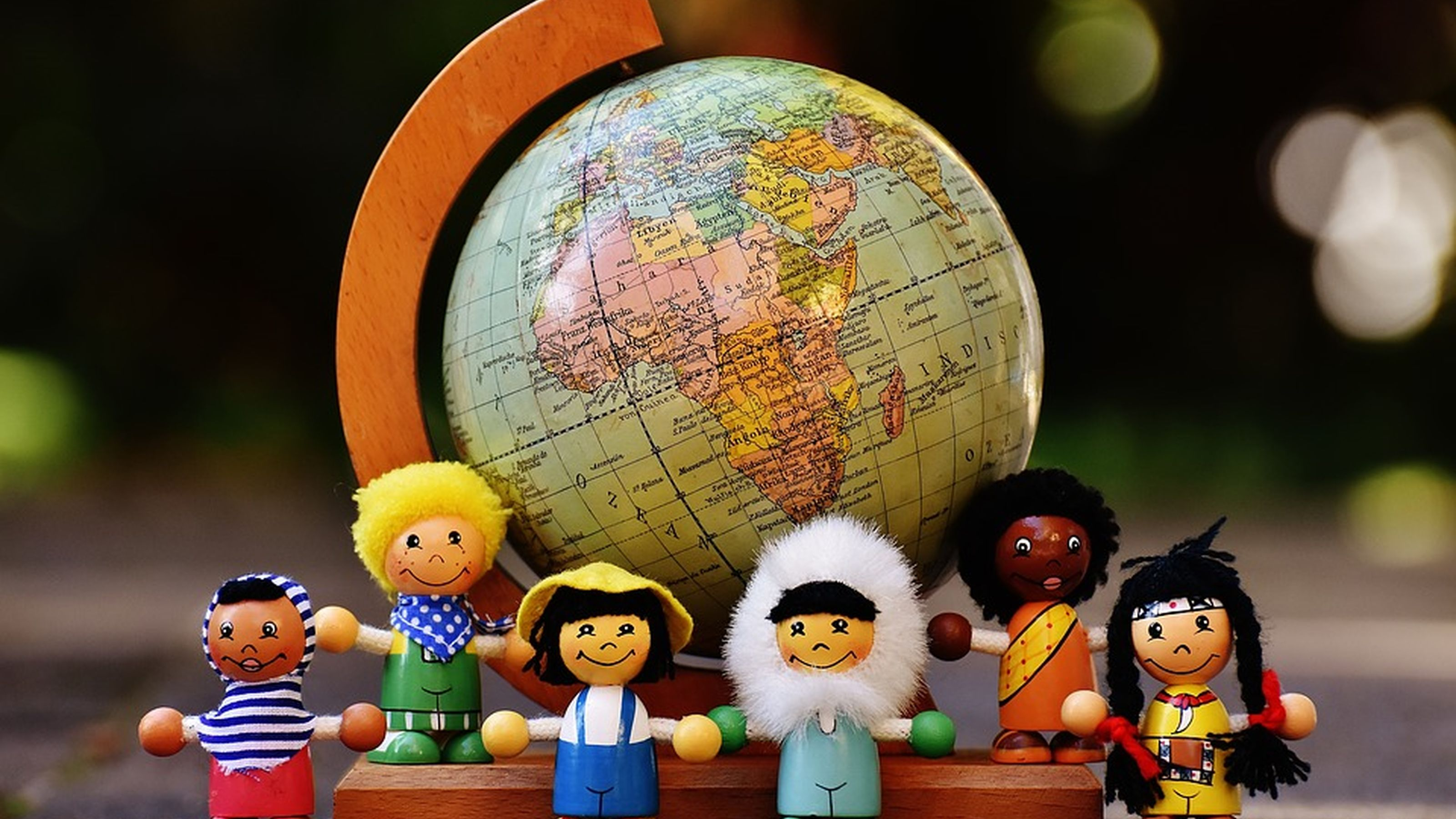 figurines from around the world standing in front of a globe