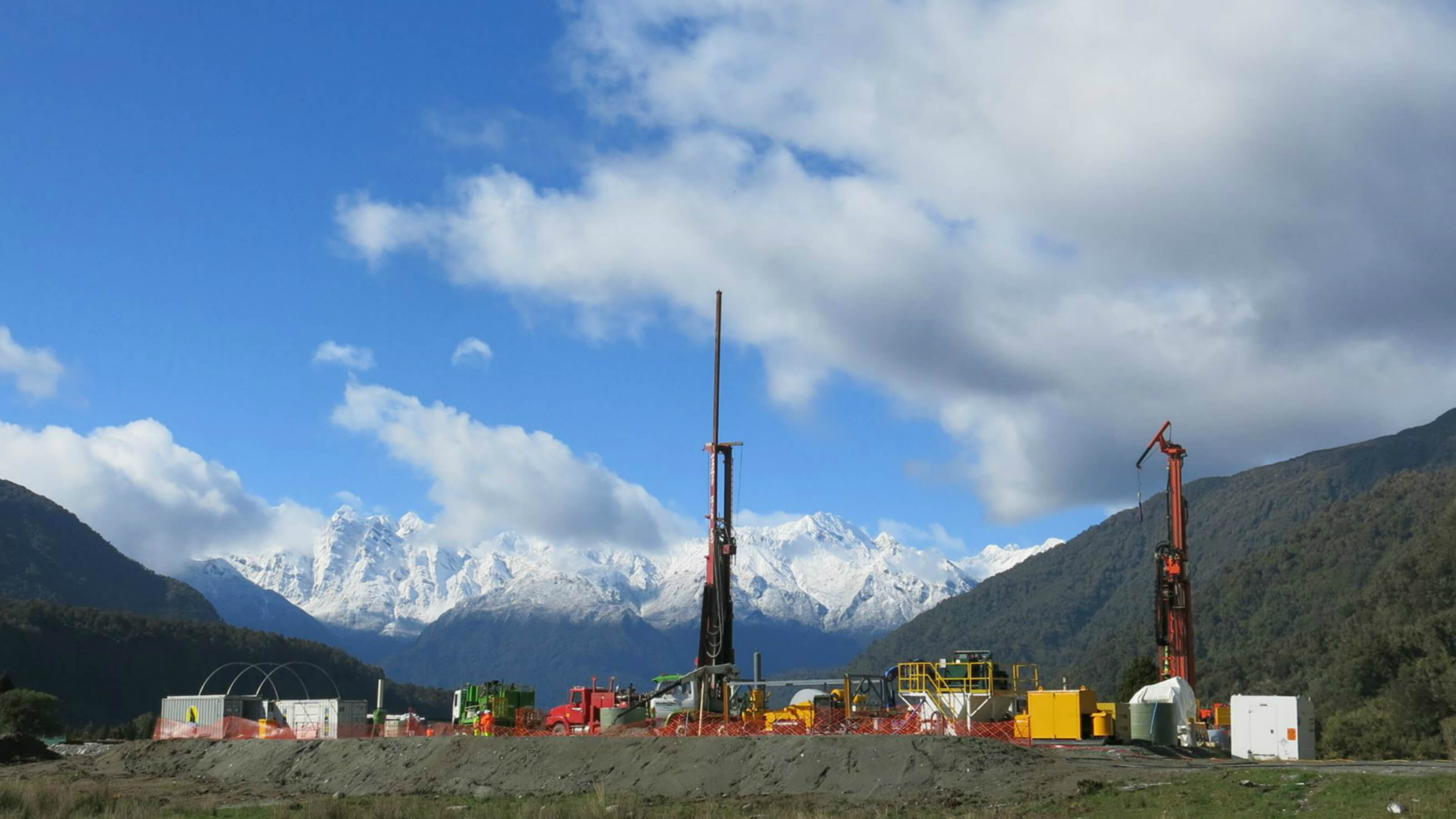 The Deep Fault Drilling Project, with a tall piece of drilling apparatus in the middle. The Southern Alps are in the background.