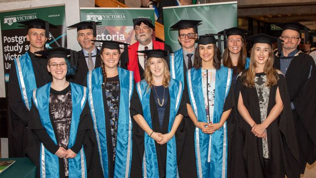 The eight meteorology graduates, wearing graduation gowns and caps, stand in front of Victoria banners with the MetService CEO and the Programme Director